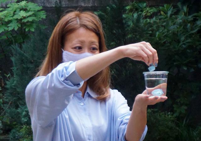 画像: E8 Sportの防水性能を確認してもらうために、コップに張った水の中に入れるというデモも実施