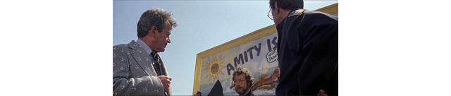 画像: フーパーは市長にサメの大きさを語り、危険を警告する 看板を隠した配置の中で、一刻を争う緊迫感、そして看板に描かれた恐怖が強調される