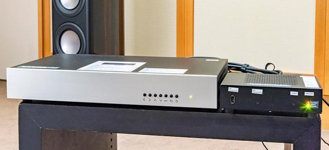 画像: 8Kデモ映像出力用として、エイム電子さんがソシオネクストの8Kメディアプレーヤー「s8」(写真左)を持参してくれた。このプレーヤーからはHDMI2.0×4本出力で8K信号を再生する仕組みなので、さらにコンバーター(写真右)を使ってHDMI2.1規格に変換、1本のケーブルでテレビにつないでいる。試聴風景の写真で麻倉さんがチェックしている映像もソシオネクストの評価用画像で8K/60p/4:2:0/HLGというフォーマットで制作されている