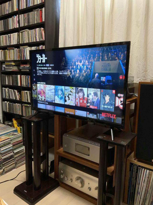 画像: 今回の視聴は自宅の仕事部屋で行なった。オーディオシステムの手前にスピーカースタンドを置き、その上に32S515を設置。NetflixやAmazon Prime Videoなどで配信系コンテンツを中心に観た