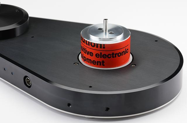 画像: プラッターを外してベース部を見る。駆動方式はコギングを極力抑えた自社設計DCモーターによるダイレクトドライブ型。電源ON/OFFと回転数切替えはワイヤレス操作。プラッターは10kgの重量級。スピンドル部にリングが装着され、レコードはスクリュー式のクランパーで圧着する。