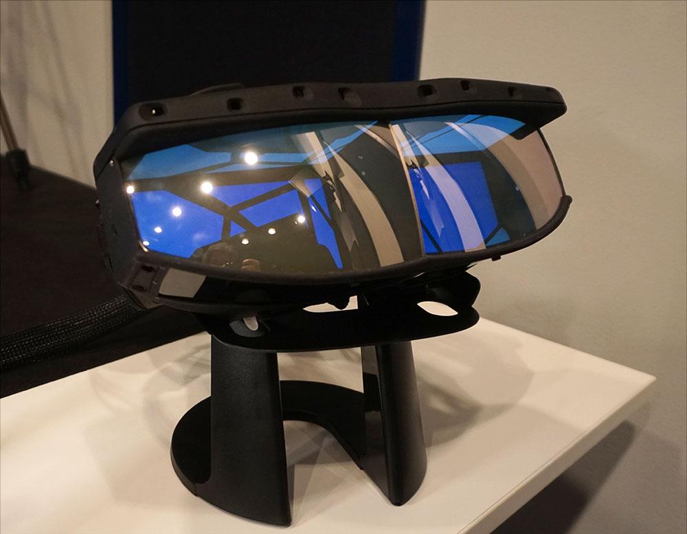 画像: ミラー式のヘッドマウントディスプレイ(写真はスタンドに載せた状態)。上側大型レンズ部の内側に映像が投写される仕組みだ