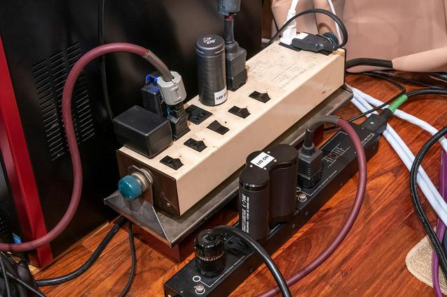 画像: 今回の視聴では、鳥居さんのシアターシステムの電源タップにマグネチックウェイブガイドを取り付けた。写真左のプロジェクター用電源タップはMC-0.5 HPS、右のパワーアンプ用にはMC-1 PRO DHPSを使い、それぞれ電源環境を改善したい機器のコンセントに一番近い空きプラグに差している