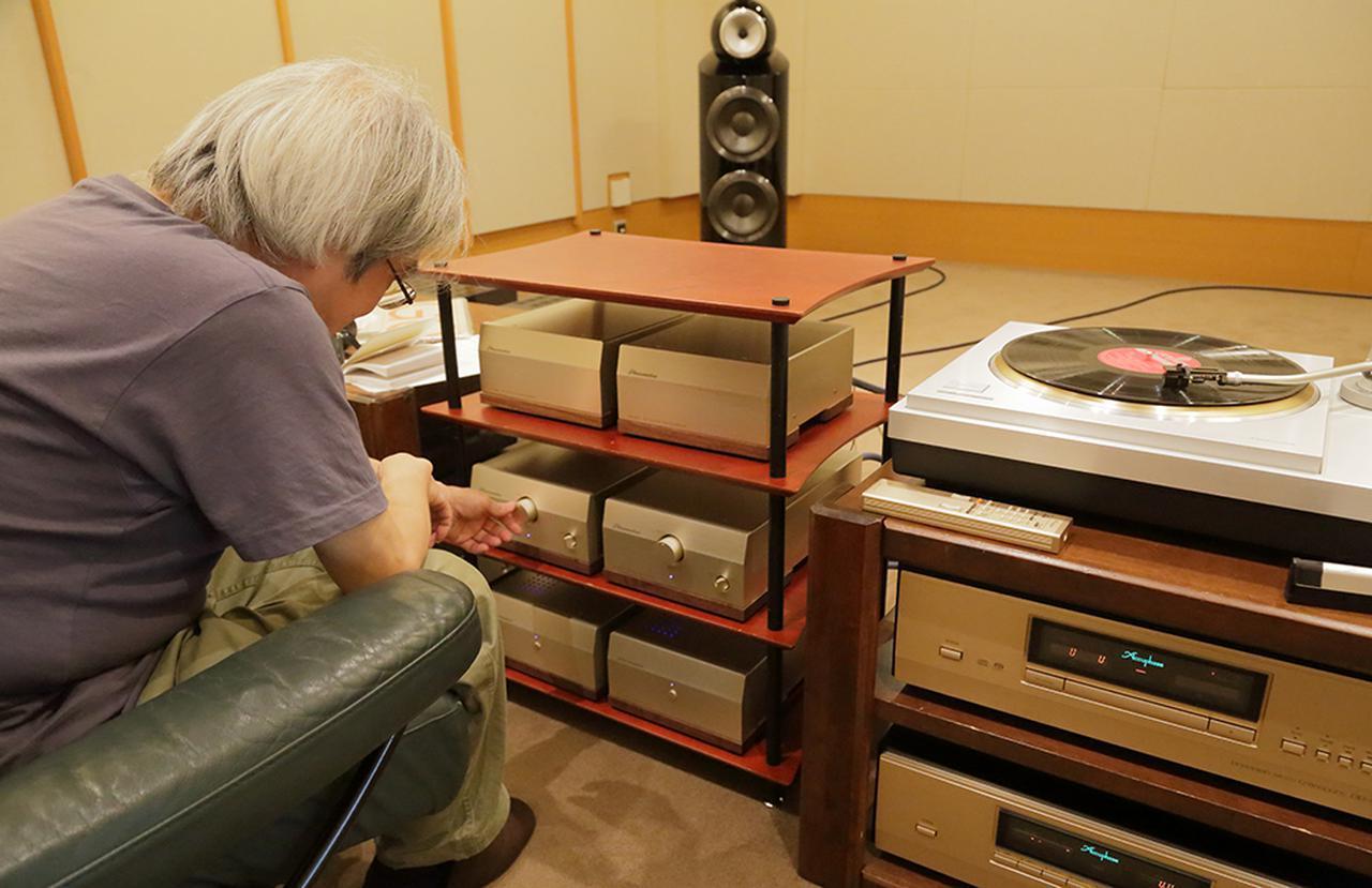 画像: 3段ラックに収めた6筐体のEA2000を試聴する吉田氏。