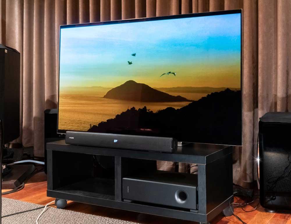 画像: ▲TOSHIBAの有機ELテレビ「55X910」と組み合わせたところ。「Stage V2」はかなり小ぶりに見えるが、画面サイズに負けないサウンドを奏でてくれた