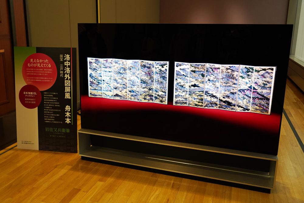 画像: ▲「洛中洛外図屏風 舟木本」の「8K文化財プロジェクト」データによる8K映像を8K有機ELディスプレイにて表示したところ。本物に比べてかなり鮮やかに仕上げられており、そのことについて担当者に聞いてみると、「完成当時の色彩を、金箔の色味を元に再現しているため」とのことだ