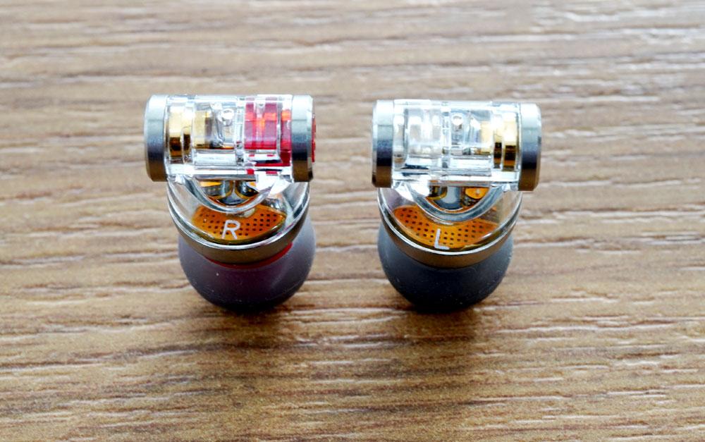 画像: イヤホン本体はT字型をしており、T字部分の両端に2種類のコネクターを装備している。本体は内部が見えるスケルトン仕様。なお、カスタム2ピンコネクターを使用時は、MMCXコネクターを塞ぐキャップも付属する