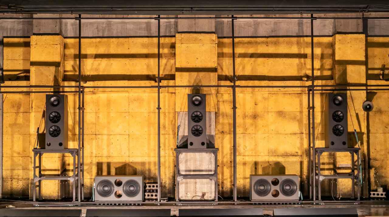画像: スクリーン裏に設置されたフロントL/C/Rスピーカーとサブウーファー2本