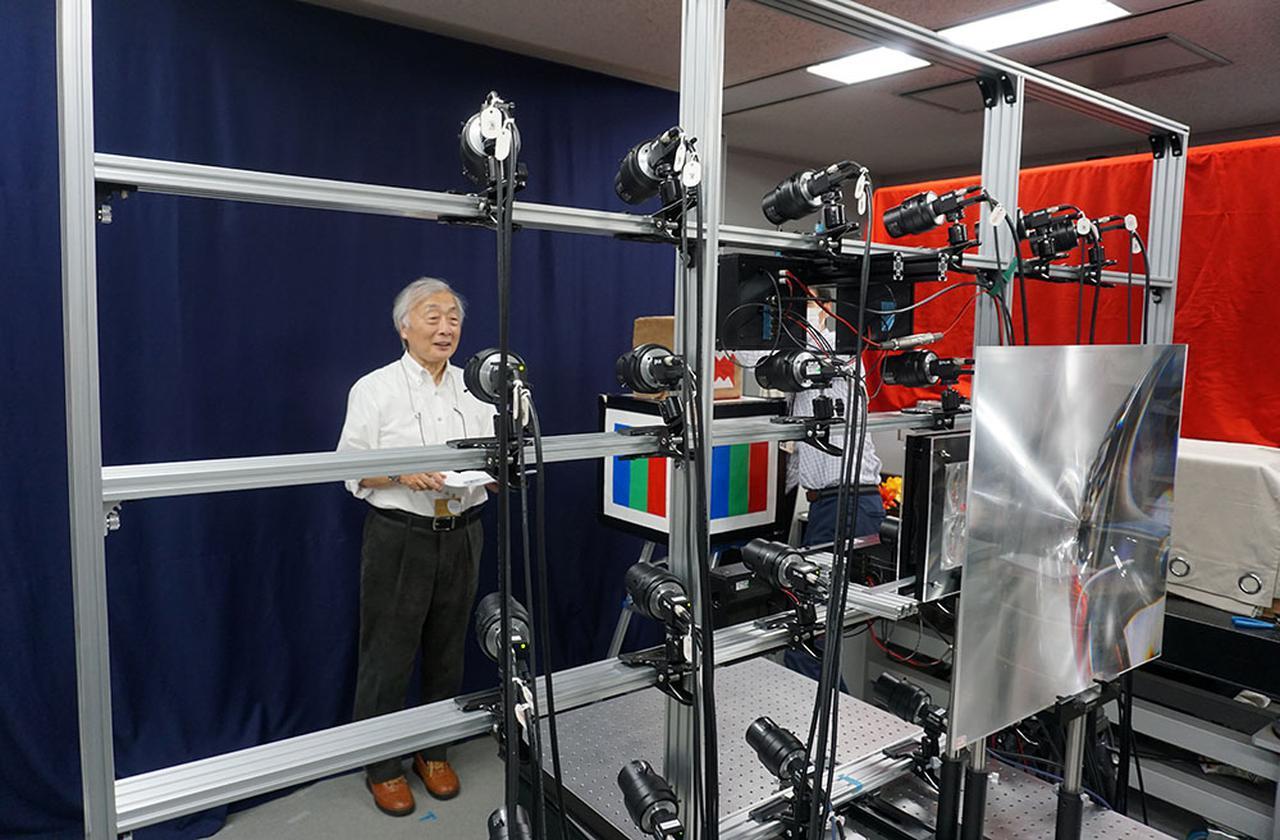 画像: アクティナビジョンの撮影用カメラの前に立つ麻倉さん。写真手前のアングルに24台のカラーカメラが取り付けられており、中央後ろのカラー・デプスカメラとの合計25台で奥行を持った映像を撮影している
