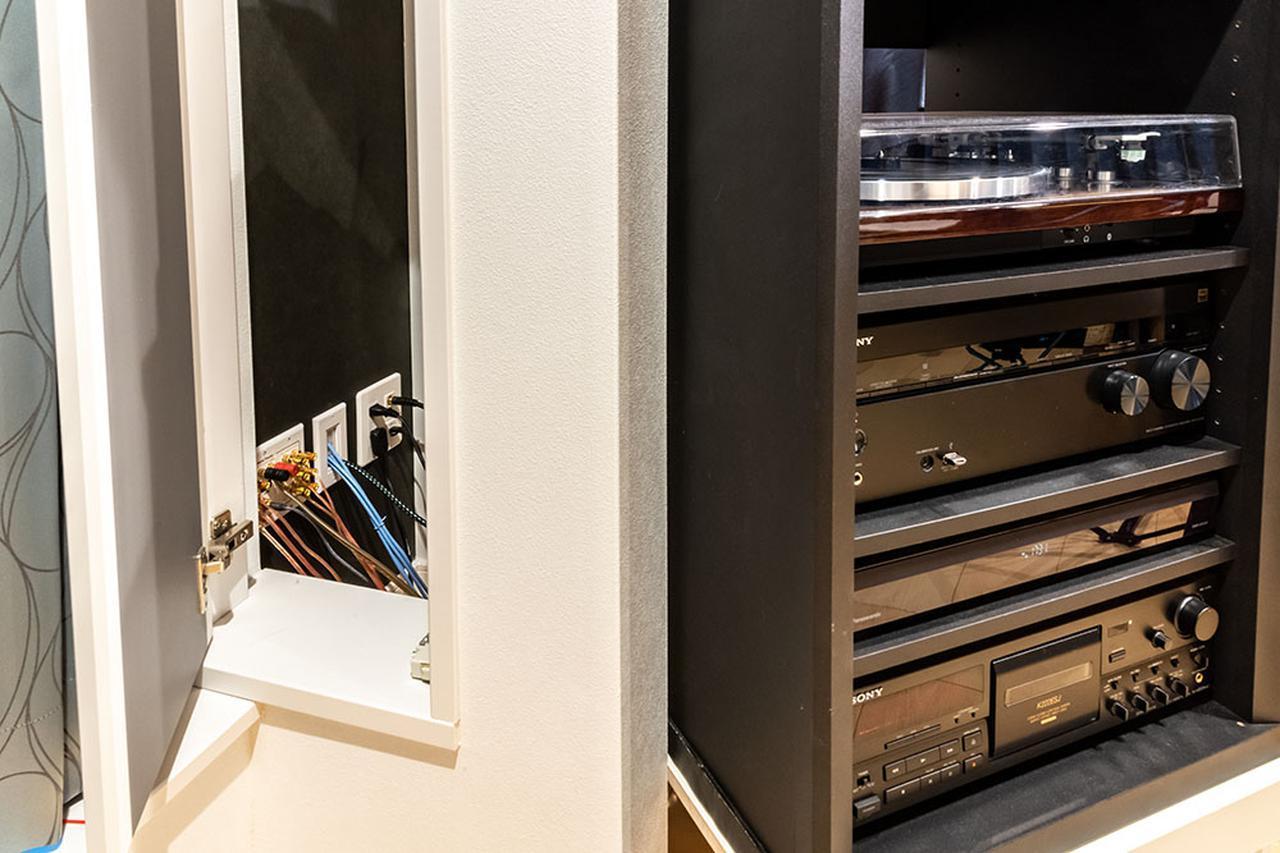 画像: ラックの後ろには、電源コンセントやスピーカーケーブル用通線用のパネルが設置されている。さらにラック横には作業がしやすいように小さな扉も準備。これも田中さんのアイデアとのこと