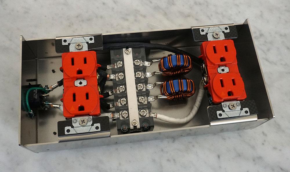画像: PB-HR550の内部構造。中央右にふたつ並んでいるのが広帯域ノイズをカットするチョークコイル。大電流用と小電流用のそれぞれのコンセントに取り付けられており、内部でノイズが回ってしまうこともない。右下にみえる内部配線材にはノイズ抑制効果を持つ素材がまかれ、その上から収縮チューブでカバーされている