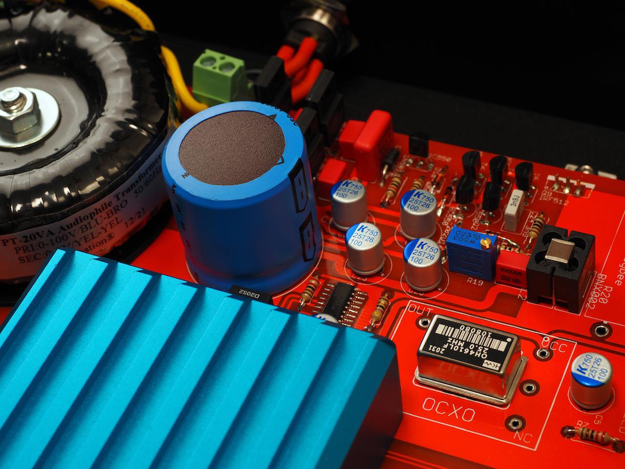 画像: 右下の四角いケースがOCXOクロック。恒温槽(オーブン)に水晶発振器を封入し、温度管理を厳密に行なうことで低ジッター化を図る、本機の心臓部ともいえる回路だ。左側には、トロイダルトランスや巨大な電解コンデンサーなどが配置されている