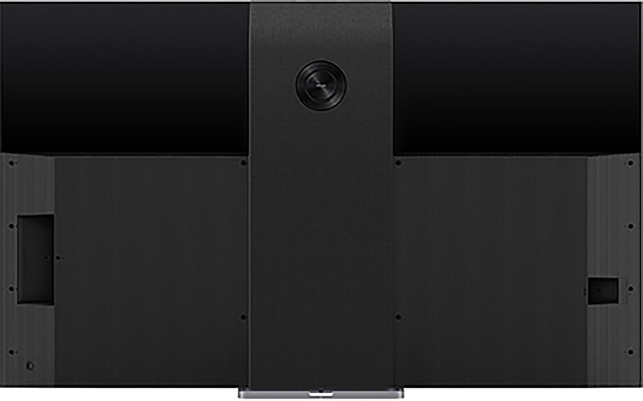 画像: 背面向かって左側に接続端子類、右側に電源ケーブル差し込み口を配置する。中央にみえるのは、サブウーファー。画面下側に開口部を前面に配置したサウンドバーとともにオンキヨー製のサウンドシステムを構成している
