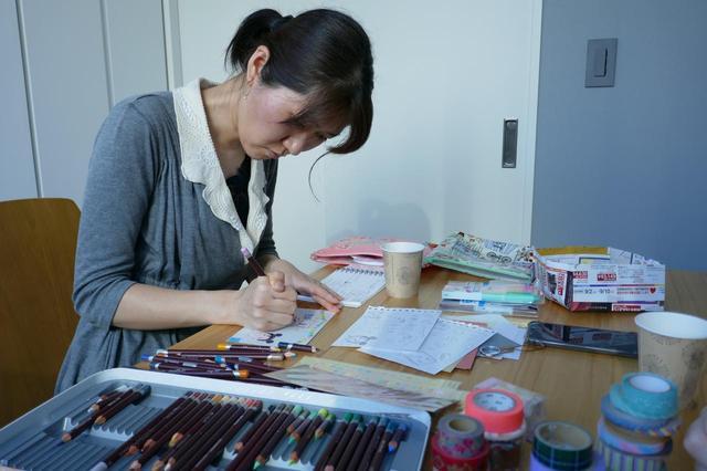 画像: 下描きを参考に、丁寧に描く竹永さん。