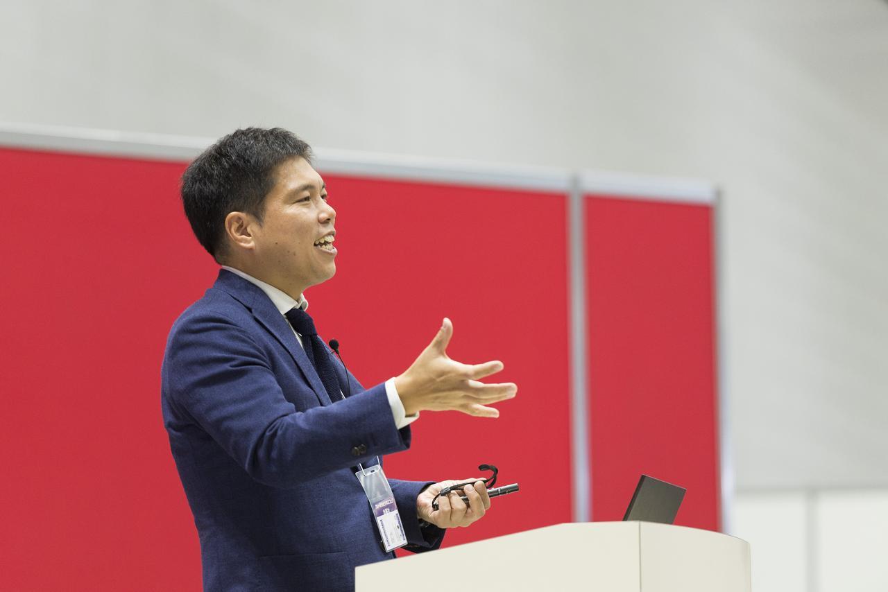 画像: ステージでプレゼンテーションする事業推進役員の加藤氏