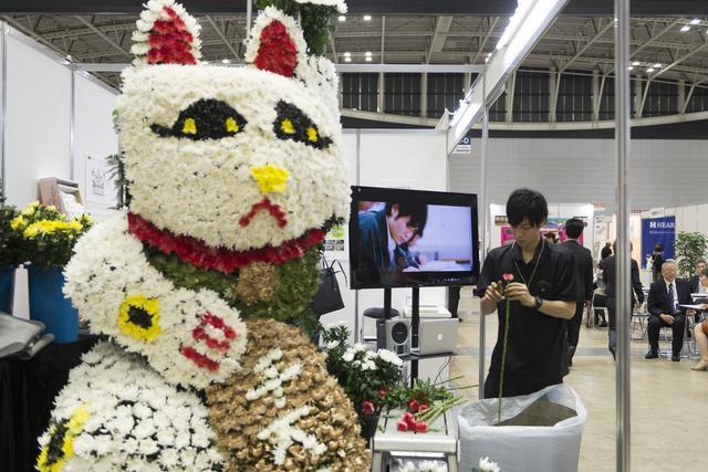 画像: 花で造られた大きな招き猫が目を引く(一社)フューネラル・フラワー技能検定協会のブース