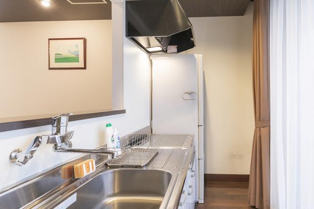 画像: ガラスのホールの反対側にはリビングがあり、オープンキッチンが併設されている