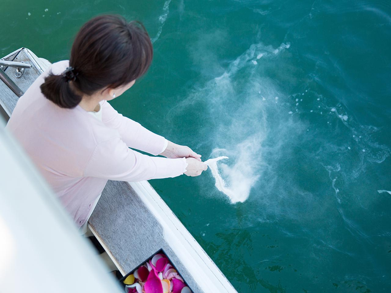 画像: 散骨場所に着いたら、参列者が順に、お骨を海に還していく