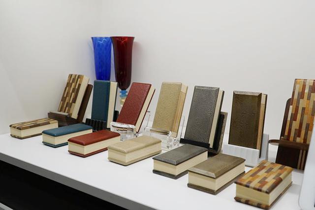 画像: モダン過去帳:手前から、箱根寄木細工で作られた「こもれび」、新潟漆器変わり塗の「朧(おぼろ)」(茶金と銀の2色)、越前塗一閑張りの「いろは」(キャメル・レッド・ブルーの3色)