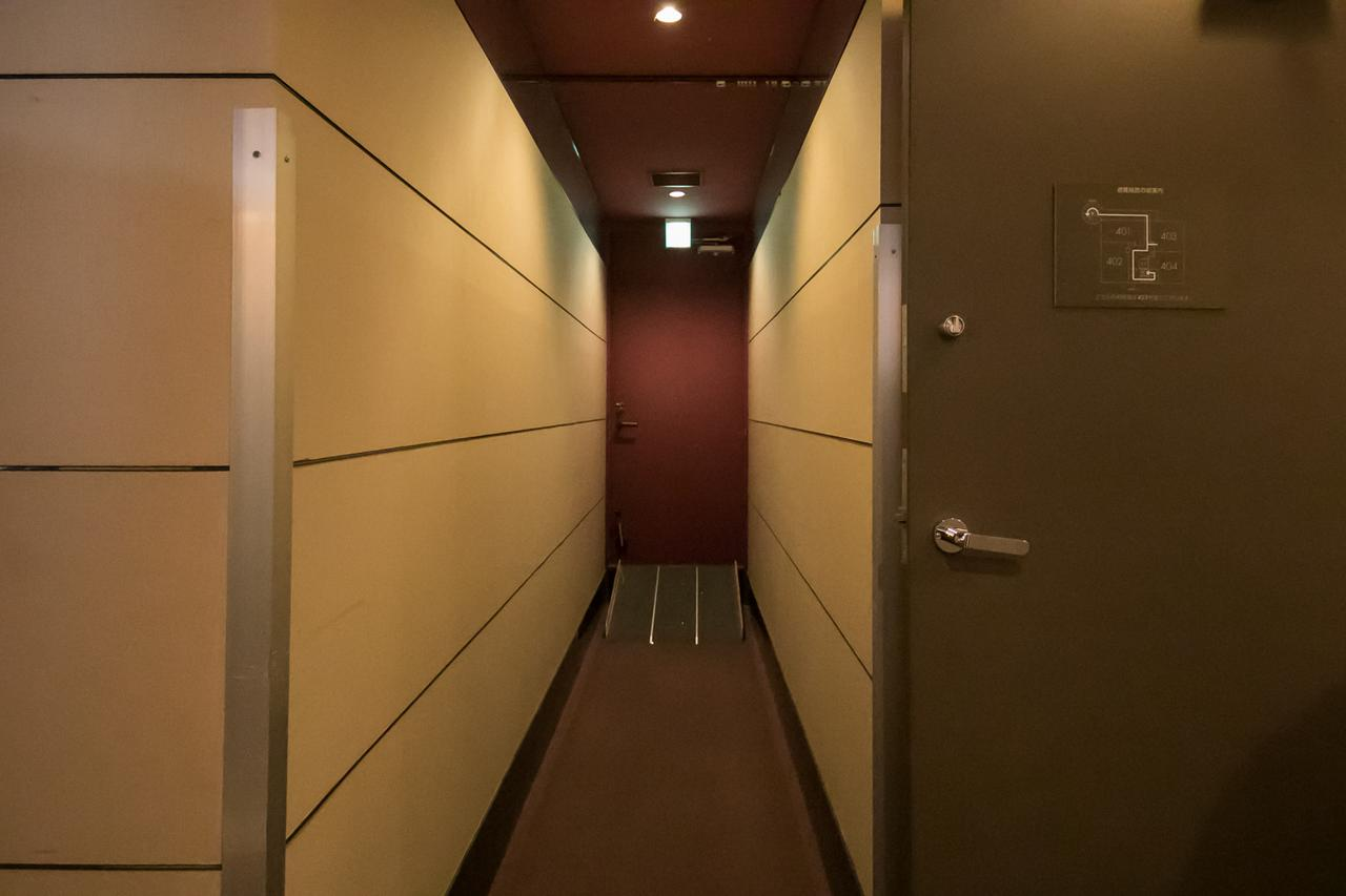 画像: 非常口に向かって、建物内部から見たところ。 廊下の角は、ストレッチャーがぶつかっても大丈夫なように補強されている