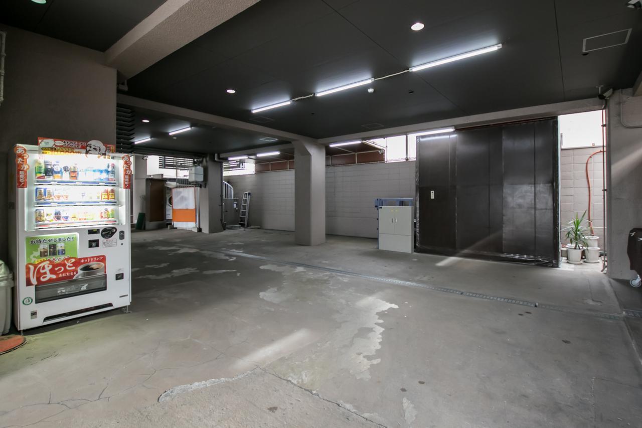 画像: 半地下の駐車場。奥に植木鉢が見えるあたり、黒っぽいカベのように見えるのが、棺用エレベーター側面