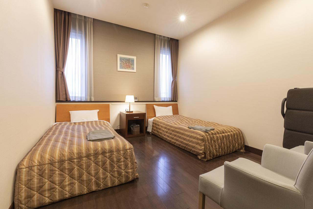 画像: ブラウントーンで穏やかにまとめたベッドルーム。 こちらも補助ベッドがある。ベッドの上に置かれているのは寝着