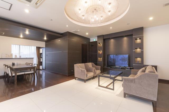 画像: 淡いグレーのソファと白い床、焦げ茶色の壁が優しいコントラストのリビング