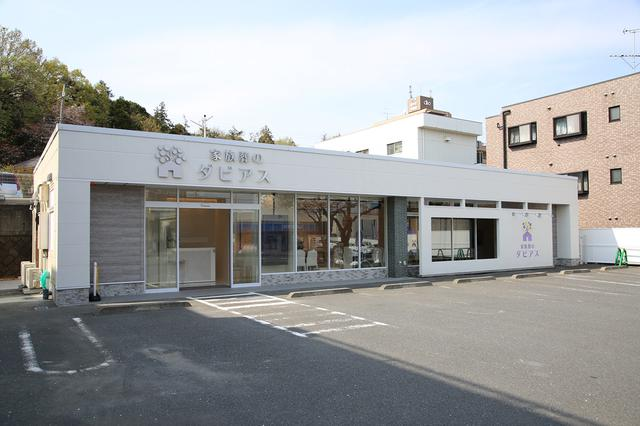 画像: コンビニエンスストアをコンバージョンした真っ白なホール 前面のガラス窓右側には白い塀が配され、くり抜いた部分が額縁となってサイネージ看板を強調