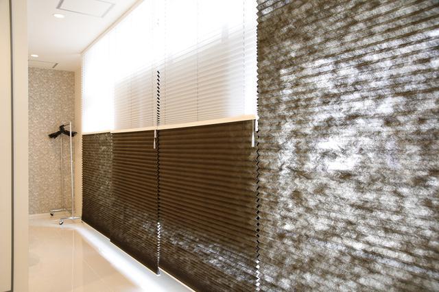 画像: ロールスクリーンは、ダークブラウンと白の2枚がつながった仕様。 式中はダークブラウンで目隠し。閉館後は中に明かりを付けた状態で白色を使用する
