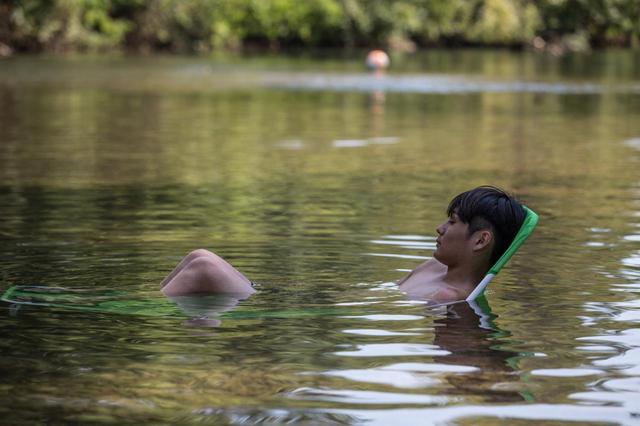 画像: 川の水で肩を冷やす下田