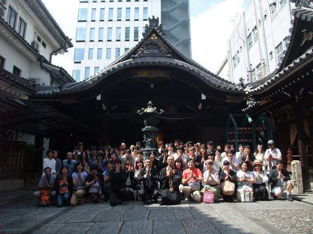 画像: MCの小早川秀樹さん、三津寺副住職の加賀俊裕さん、そしてお集まりの皆様と一緒に合掌ポーズ