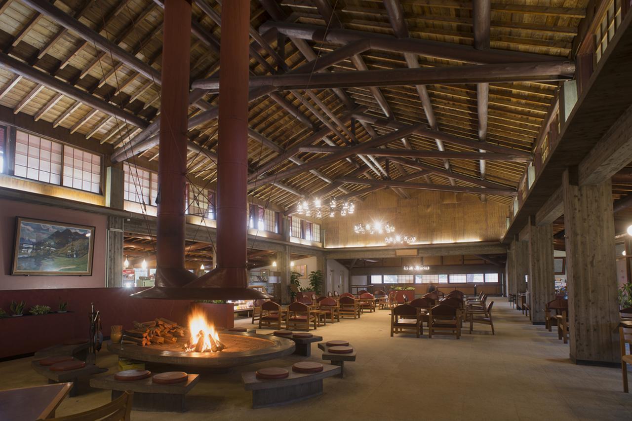 画像: 木の梁の高い天井:障子窓が外光を柔和に変える。シャンデリアやバーカウンターの椅子は妻のノエミ・レーモンドがデザイン