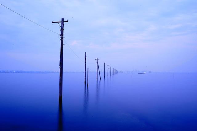 画像: 潮が満ちると何気ない砂浜は奇観へと様変わりする。海中電柱は近い将来撤去されてしまうという話も