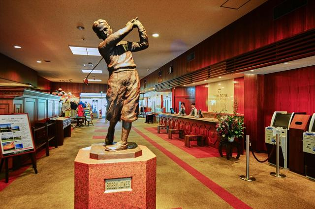 画像: クラブハウスの一階フロント。ボビー・ジョーンズの銅像がお出迎え