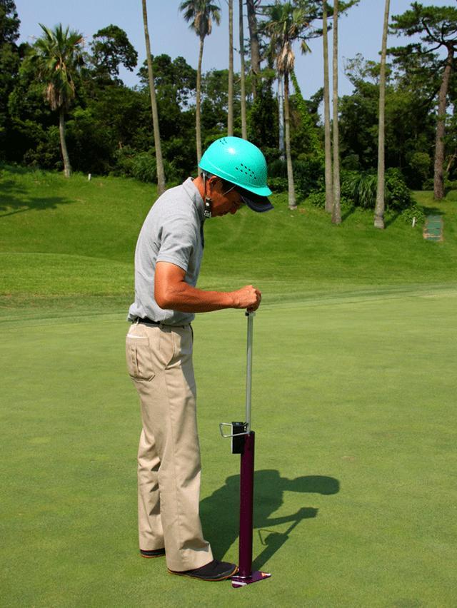 画像: 芝の根の張り具合を高めるために、発根促進資材を試験中。手にする器具でコンパクションを測る