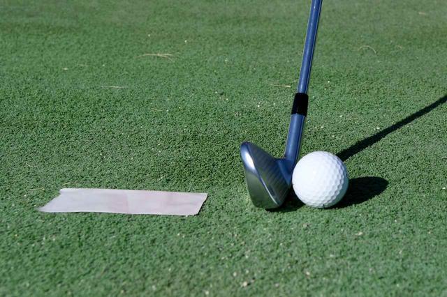画像: ボールの手前に10センチくらいの長さに切り取ったガムテープをマットに貼りつけて練習しよう。マットの場合、手前をダフってもヘッドが滑りやすいため、グッドショットになることが多く、ダフっていることに気づきにくい。番手は7番アイアンで練習しよう