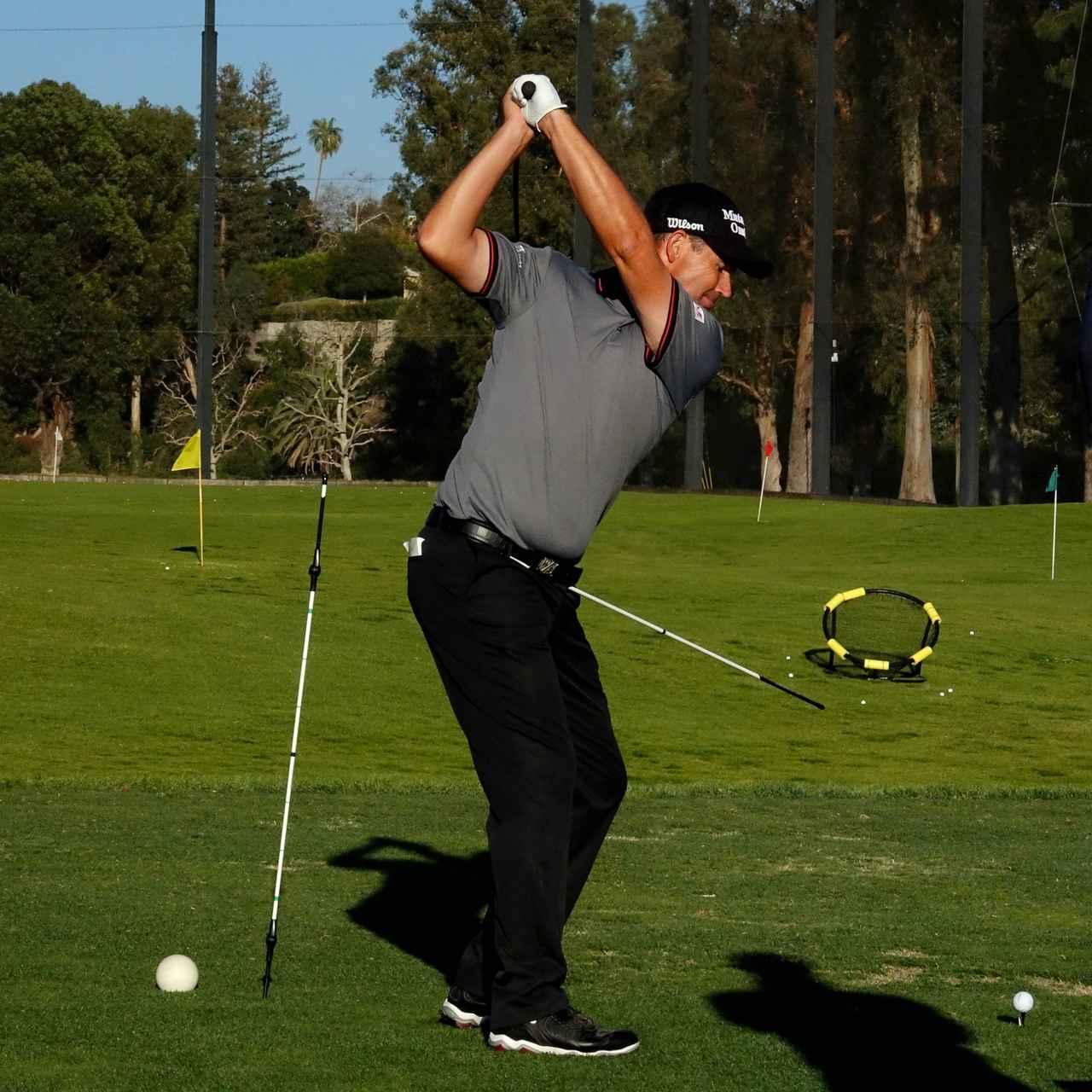画像: ①フォローサイドの左腰側に、自身の腰の高さに合わせた棒を立て、腰に差した棒を回し当てる