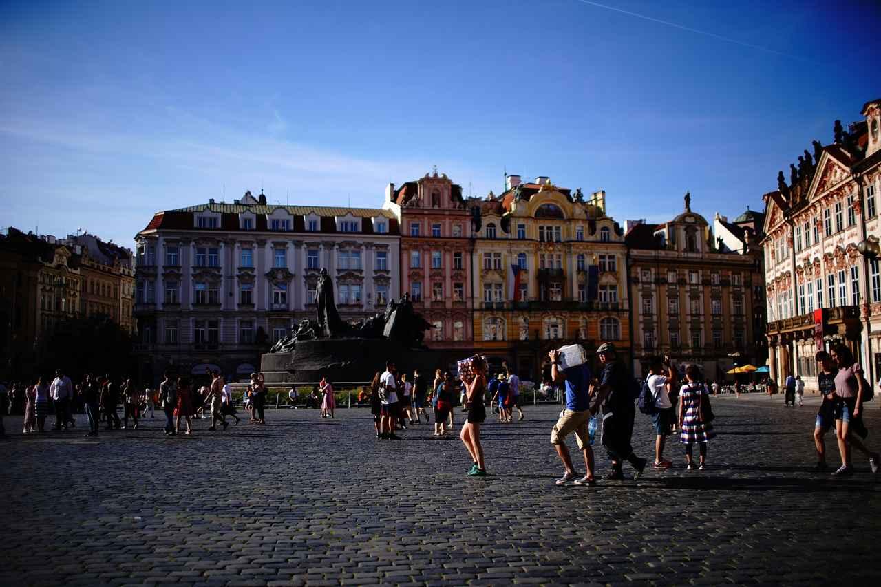 画像: いろいろな時代の建築物に囲まれた旧市街広場。中央に建つのはチェコの宗教改革の先駆者「ヤン・フス」像