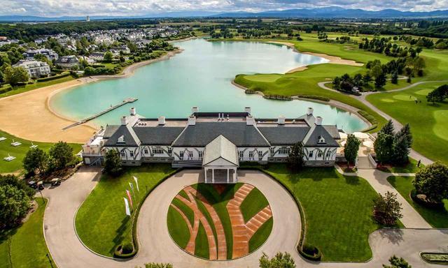 画像: 宮殿のようなクラブハウスの前には湖が広がる