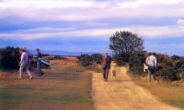 画像: ゴルフコースの脇を小径が通る。ボールを探すゴルファーと散歩中の翁が交錯するのも、セントアンドリュースならではの光景だ