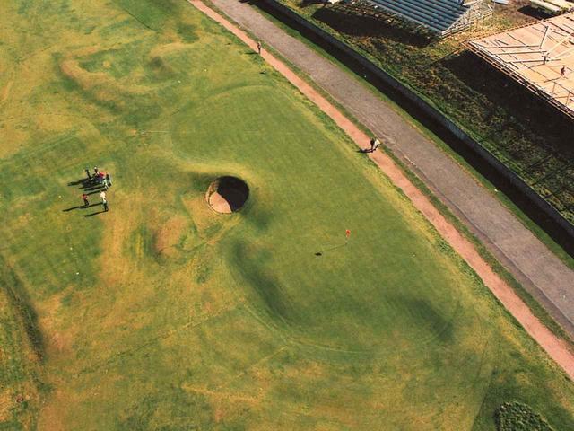 画像: グリーンのすぐわきが地道、その隣はアスファルト。ボールが止まればそこから打つしかない