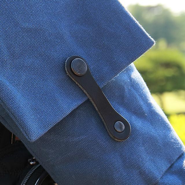 画像: 上部分フラップを留めるスナップボタンは、栃木レザーと真鍮ボタンを採用