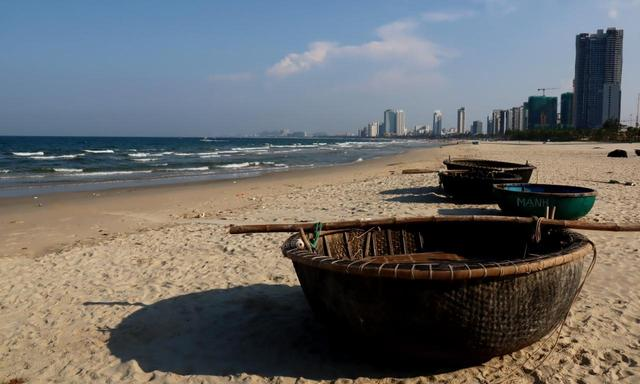 画像: ダナンビーチ。イカ・エビ漁の小舟が並ぶエリア。遠くには建設中のホテル