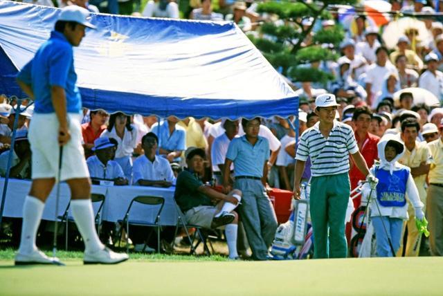 画像: グリーン上でプレーする尾崎将司と直道。後ろのテントには建夫の姿も