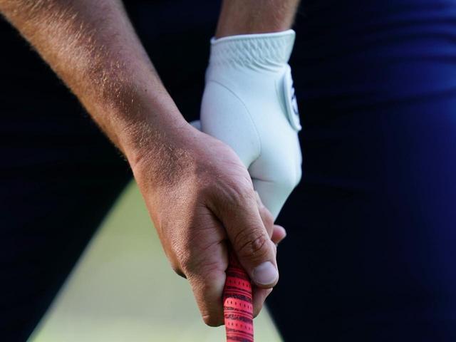 画像: 左手の甲が飛球線を向く。人差し指の腹でボールを押せる形。両手を絞るように握っている