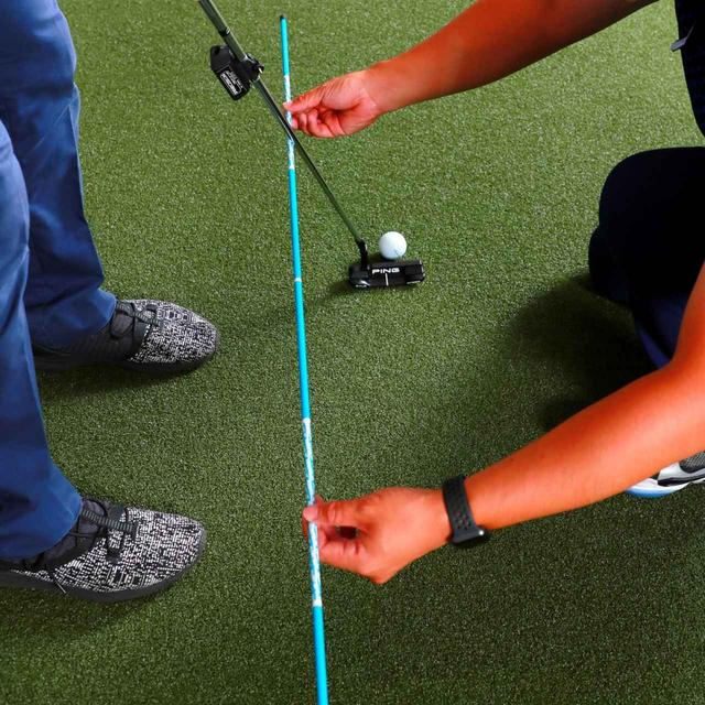 画像: ストロークラインと平行にアライメントスティックを持ってもらい、スティックにそって素振りを繰り返せば正しいスウィング軌道が身につけられる