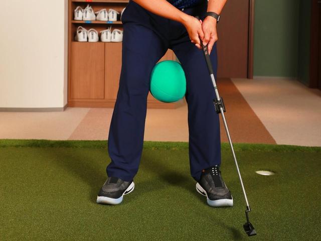 画像: 両足にバランスボールを挟んでパッティング。足が動けばボールが落ちるため、両足を固定して打つことが身につく。下半身を安定させるのに効果的