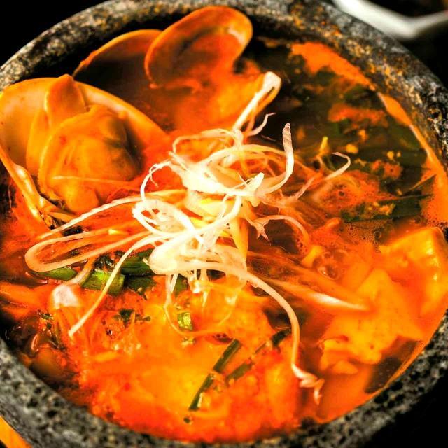 画像: 柔らかい汲み出し純豆腐に白菜、ニラ、ネギ、アサリ、ハマグリと具だくさん。白菜と切干のキムチ、季節の自家製キムチ、ご飯付き