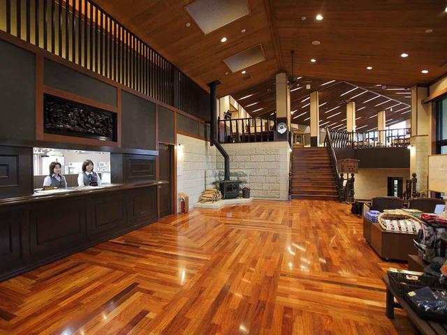 画像: 木造を思わせる木目の床材と小振りなフロント。リゾート感溢れるロビー