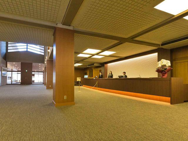 画像: 広々としたロビー。フロントカウンター、柱とすべて木目調の装飾で落ち着きが感じられる